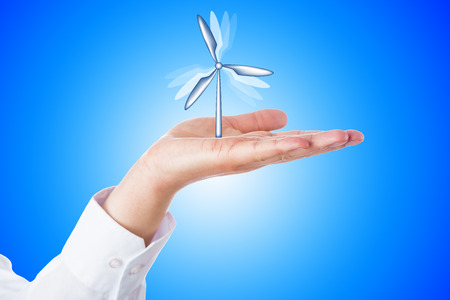 greenhouse gas: Vertical wind turbine turning its rotor blades while firmly moored in the open palm of a horizontal hand. Close up over sky blue background with bright gradient center. Wind energy business concept.