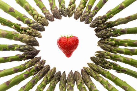 inwards: Many green asparagus spears arranged to a circle. Tips pointing inwards to a heart-shaped strawberry in the center. Cutout isolated on white. Selective focus on the fruit and front half of the ring.