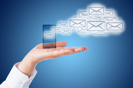 email: Many email icons leaving a smart phone to shape a cloud computing symbol. The mobile device is resting in the open palm of a hand of a business man. Blue background with smooth gradient. Close up. Stock Photo