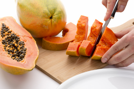 halved  half: Halved papaya fruit being cut into slices with a sharp kitchen knife on a wooden cutting board. Half a pawpaw fruit and an entire papaya placed next to it. Orange colored fruit pulp. White background.