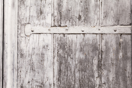 mountings: Close up on the weather-worn surface of a wooden window shutter. The texture of peeling paint is overlaying the vein of the wood. Iron mountings running horizontally across. Outdoor shot on tripod. Stock Photo