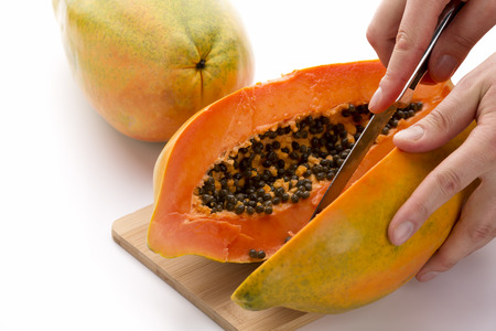 Papaya cut in half along the longitudinal axis of its oblong shape.