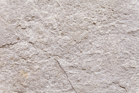 man made structure: Rough surface texture of a weathered block of stone set into the exterior wall of an ancient building. Flat background for two-dimensional spatial compositions. Close up shot outdoors on a tripod. Stock Photo