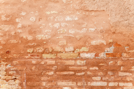 sienna: Porous surface texture of an old exterior brick wall. Background with patina of crumbling Venetian red plaster. Hints of ocher and burnt sienna color hues. Cracks showing. Outdoor shot on a tripod.