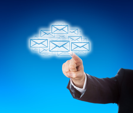 technology metaphor: Forearm in blue corporate suit is reaching out to touch a swarm of emails in the shape of a cloud. Business or technology metaphor for mobile computing and instant information access. Copy space. Stock Photo