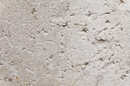 two dimensional: Close up on opened-up cracks in the weathered plaster of an ancient exterior wall. Rough, porous stone surface with aging patina. Beige and gray color with rust brown freckles. Texture for background.