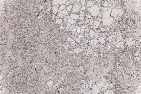 weatherworn: Close up on the brittle texture of plaster covering an exterior load-bearing wall. Porous surface, weather-worn patina. Two-dimensional architectural detail for background use. Gray color with spots.