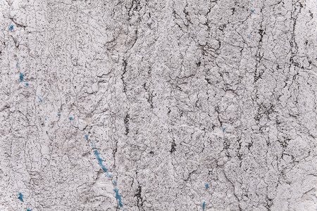 fissures: Brittle texture of a weathered ancient block of stone in an exterior load-bearing wall. Pale gray and light beige color. Black fissures, cracks and veins. Some blue paint stains. Flat background. Stock Photo