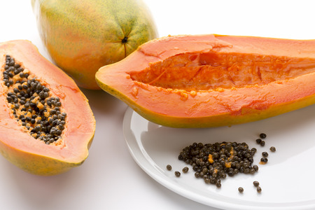 countless: Hollowed out half of a raw papaya in longitudinal cross section and its countless peppery seeds on a white plate. Succulent breakfast fruit of the tropical Carica papaya. Close up. White background. Stock Photo