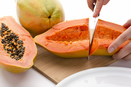 cut through: First cut through a hollowed out half of a papaya. Finger tips of the left hand of a chef are fixing the fruit on a wooden cutting board, while his right is guiding a kitchen knife. Cutout. Close up.