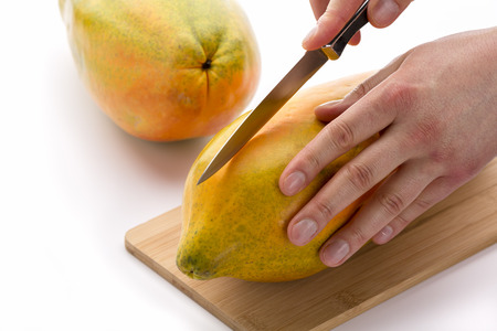cut through: Kitchen knife positioned for a first cut through a papaya along its longitudinal axis. The left hand of a chef is placing the tropical fruit on a cutting board, while his right is guiding the blade.