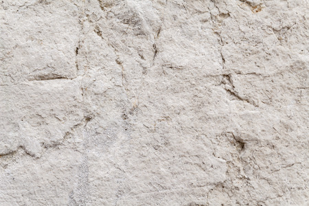 pale color: Uneven surface texture of a weathered ancient square stone in an exterior load-bearing wall. Brittle, eroded rock patina with beige and pale color hues. Architectural detail for background. Close up.
