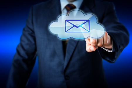 technology metaphor: Upper body of a business man in suit reaching forward to touch an email icon in a cloud symbol. Technology metaphor for mobile computing and contemporary working environment. Blue colors. Copy space. Stock Photo