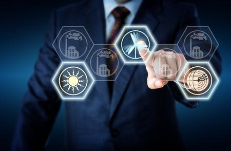 eficiencia: Torso de un gerente corporativa en traje de negocios llegar a tocar un icono de la energía eólica. El símbolo viento activo está iluminando junto con un botón de la energía solar y geotérmica. A su vez la metáfora de la Energía.