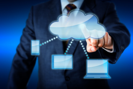 synchronizing: Upper body of a business man in blue suit is touching a blank cloud icon at the heart of a smart computing network. Cell phone, tablet computer and laptop are all linked to the cloud. Copy space. Stock Photo