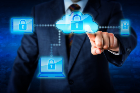 closed lock: Torso of a business man in blue suit reaching forward to touch a cloud icon with index finger and lock mobile devices. Smart phone laptop and tablet PC are in the cloud network. Technology metaphor. Stock Photo