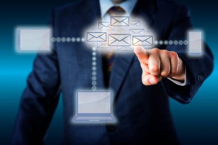 email icon: Business manager in blue suit touching a swarm of emails shaping a virtual cloud at the center of a wireless computing network. Laptop smart phone and tablet computer are linked to the email cloud.