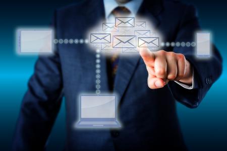 centro de computo: Gerente de negocios en traje azul de tocar un enjambre de correos electr�nicos que dan forma una nube virtual en el centro de una red inform�tica inal�mbrica. Tel�fono inteligente para port�til y Tablet PC est�n vinculados a la nube de correo electr�nico. Foto de archivo