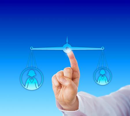 balanza en equilibrio: Primer plano de una mano tocando una balanza virtual para equilibrar un trabajador de oficina femenina de peso pesado contra un compañero femenino ligero. Metáfora del asunto para el éxito profesional y la competencia. Foto de archivo