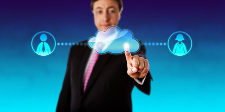business metaphor: Smiling businessman is touching a virtual cloud to contact one female and one male white collar worker in cyberspace. Business metaphor and technology concept of connectivity and cloud computing.