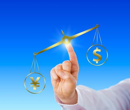 financial metaphor: Dedo �ndice de un hombre de negocios se est� posicionando una escala de oro virtual en el espacio. El signo yen japon�s contrarresta el s�mbolo del d�lar en el par de saldos. Met�fora financiera para el comercio de divisas. Foto de archivo
