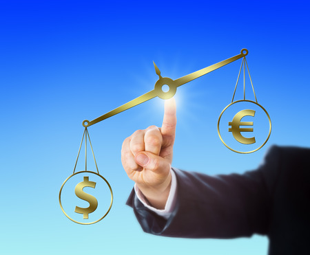 financial metaphor: US Dollar sign is outweighing the Euro symbol on a golden balance. Index finger of a businessman is operating this virtual weighing scale in mid-air. Financial metaphor for foreign exchange market.
