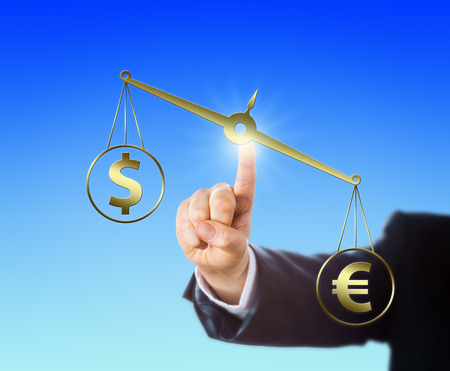financial metaphor: Euro currency sign is outweighing the Dollar symbol on a golden balance. Index finger of a white collar worker is touching this virtual weight scale and positioning it in space. Financial metaphor. Stock Photo