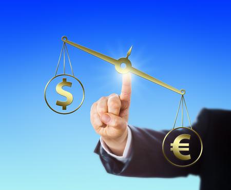 financial metaphor: Euro signo de moneda contrarresta el s�mbolo de d�lar en una balanza de oro. Dedo �ndice de un trabajador de cuello blanco est� en contacto con esta escala de peso virtual y posicionarlo en el espacio. Met�fora financiera.
