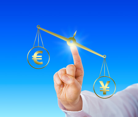 lopsided: Japanese Yen sign is outweighing the European Union currency symbol on a golden virtual balance held in position by an index finger. Concept for the structure of the international currency market.