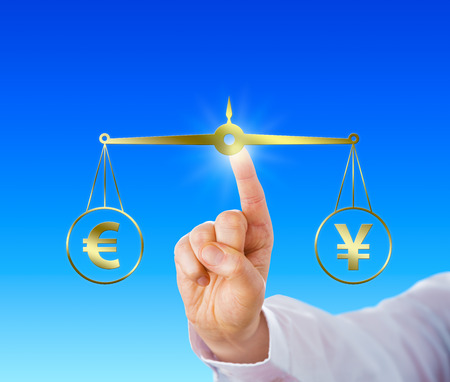 parity: Index finger of a white collar worker is equating the European Union currency sign at par with the Japanese yen symbol on a virtual golden scale over light blue background. Financial metaphor. Stock Photo