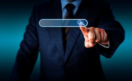 dedo indice: Torso de hombre de negocios empujando hacia adelante con la mano izquierda para tocar un icono de lupa en una barra de búsqueda virtual con su dedo índice. No colocar el texto en el cuadro de búsqueda vacío. Fondo con el espacio de la copia.