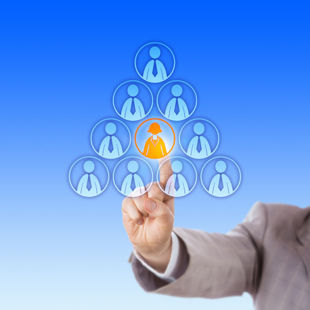 hierarchical: Arm in light grey suit reaching out to select a single female office worker icon by touch at the center of a pyramid made of male employee symbols. Business metaphor for discrimination and hierarchy. Stock Photo