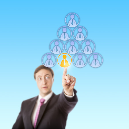 pyramidal: Focused manager is reaching up to single out by touch a male office worker at the bottom of a pyramidal hierarchy of male worker icons. Business metaphor for headhunt, success or discrimination.