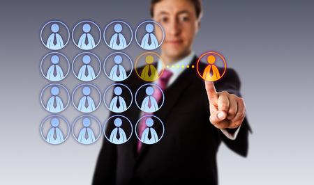 competencia: Encargado sonriente que está tocando un solo hombre blanco icono de trabajador de cuello fuera de un grupo organizado de iconos masculinos de los empleados. Metáfora del asunto para el outsourcing, el crowdsourcing, contratación y contratación. Foto de archivo