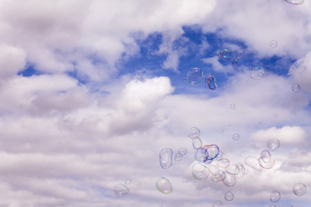 gust: Many soap bubbles floating in a gust of wind before white clouds over blue sky. Asymmetrical, soft background with copy space. Handheld outdoor shot in bright, albeit diffused, daylight.