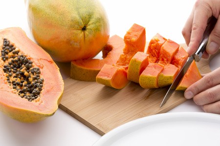 exert: Cutting a quarter of a papaya into six slices with a short kitchen knife. An entire fruit and a half are placed to the side. Juicy tangerine colored fruit pulp covered in lime green skin. Close up.