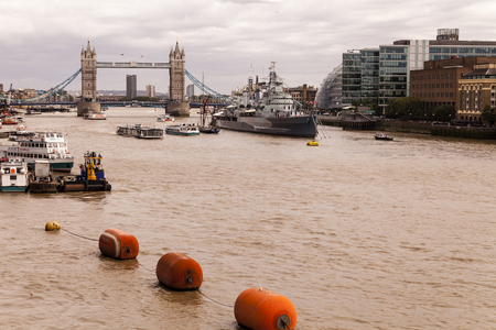 hms: Editorial: London, United Kingdom - August 04, 2015: River Thames flowing eastward past the moored HMS Belfast towards the Tower Bridge. Shot from London Bridge on an overcast Summer afternoon.