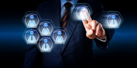 dismantle: Torso of a consultant is dismantling a work team in cyber space. His left hand is moving a female and a male worker icon away from the group in a swiping gesture with raised index and middle finger. Stock Photo