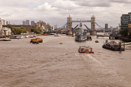 eastward: London, England, United Kingdom - August 04, 2015: Battleship HMS Belfast moored in front of the Tower Bridge amidst the River Thames flowing eastwards. Shot from the south end of London Bridge.