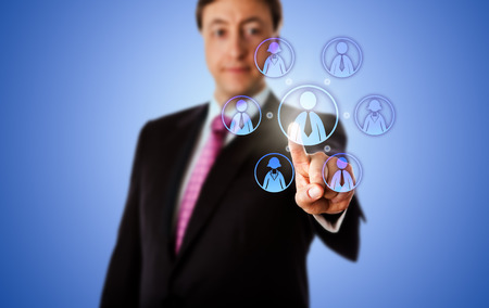 knowledge business: Smiling business consultant is contacting a virtual work team by touch. The team has a male team leader and three female and male knowledge workers. Metaphor for remote work force in cyber space. Stock Photo