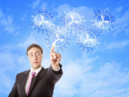 turnaround: Entrepreneur intently looking at a virtual gear train formed by five cog wheels. Each gear wheel does carry a wind power icon. Business concept for energy turnaround through wind energy generation.