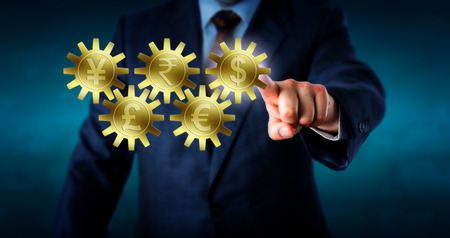 Five major currencies interlocking like a gear train. Golden cogs embossed with Dollar, Euro, Rupee, Pound Sterling and Yen or Yuan symbol. Hand of a trader is touching and highlighting the Dollar. Stock Photo