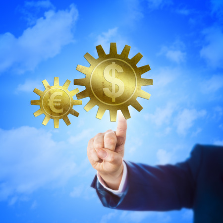 financial metaphor: Big golden cogwheel carrying the Dollar symbol is interlocking with a small gear wheel embossed with the Euro sign. Hand of a trader touching the larger cog. Financial metaphor for currency exchange.