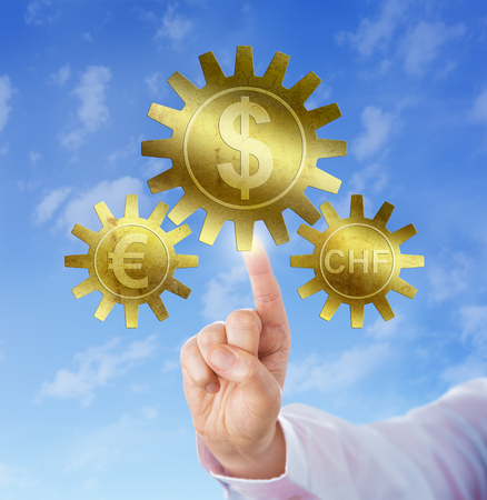 european union currency: European Union currency and Swiss franc pegged to the dollar. The dollar sign is embossed onto a large golden cog and the euro and franc symbol are carried by small gearwheels. Financial concept. Stock Photo