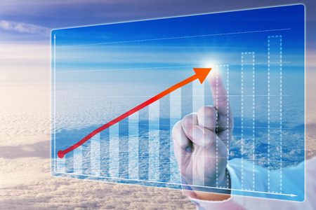 business trending: Index finger touching a growth trending arrow in a virtual bar chart. The graph is displayed on a touch screen interface hovering in space high above the clouds. Concept for business forecasting. Stock Photo