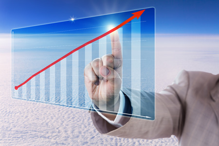 business trending: Arm of a business manager is reaching out to touch a red growth trend arrow in a virtual bar chart. Touch screen interface is hovering in mid-air, overlooking a dense cloud front from high above. Stock Photo