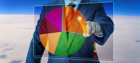 exploded: Torso of a manager is segmenting a pie chart high above the sky on a virtual touch screen interface. The largest sector is separated from the rest of the disk, i.e. the orange sector is exploded. Stock Photo