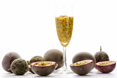 champagne flute: Passionfruit pulp and seeds in a champagne flute. The glass is standing amidst many halved and whole ripe passion fruits of the purple granadilla variety. Close up studio shot over white background. Stock Photo
