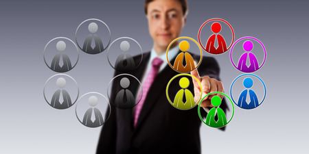 equal opportunity: Happy manager selecting a multicolored team of male workers over a plain, gray group. Business concept for diversity, equal opportunity employment and team building in a multicultural organization.