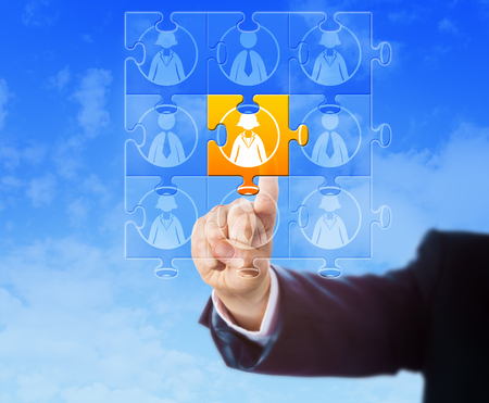 on cloud nine: Hand selecting a female worker icon that is part of a jigsaw puzzle. Each puzzle piece is displaying a male or female knowledge worker symbol. Business metaphor for career success and teamwork.